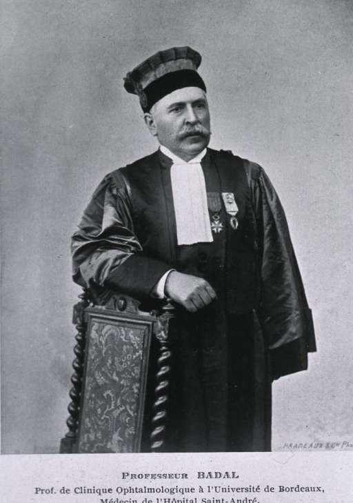 <p>Three-quarter length, standing, arm resting on chair back, wearing robe and cap.</p>