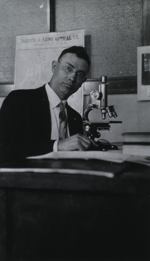 <p>Seated in office with microscope in front.</p>
