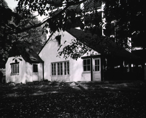 <p>Exterior view of Top Cottage showing Building 31 under construction in the background.</p>