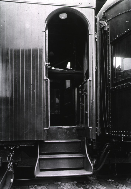 <p>Through an open doorway, a patient on a stretcher is seen being passed between the cars of a hospital train.</p>