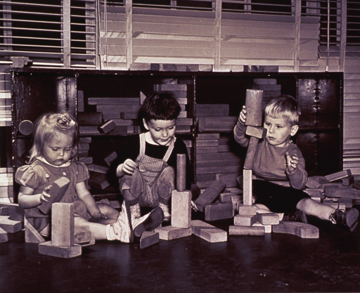 <p>Three children are playing with wooden blocks.</p>