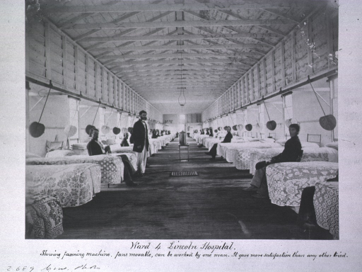 <p>Interior view of a long wooden structure with exposed beams and a row of beds on each side with several patients sitting and/or standing near their beds. This is hospital ward no. 4 of the U.S. Army's Lincoln General Hospital, Washington, D.C.</p>
