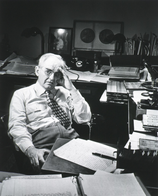 <p>Half-length, seated at desk, right pose, full face; wearing glasses; hand to head.</p>