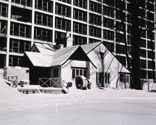<p>Wintertime photo of Top Cottage showing Building 31 under construction in the background.</p>