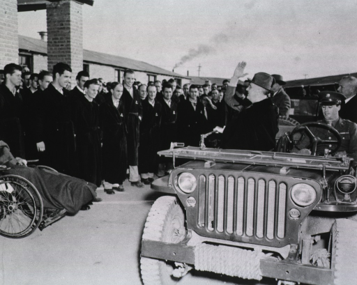 <p>From the front passenger seat of an open-air jeep, President Roosevelt greets patients standing in front of the hospital.</p>