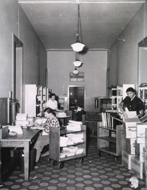 <p>Interior view: In the binding section material is in boxes, on book trucks, on shelves, and stacked on the table. Bindery staff is preparing the material for the shelf.</p>