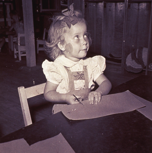 <p>A little girl is cutting paper.</p>