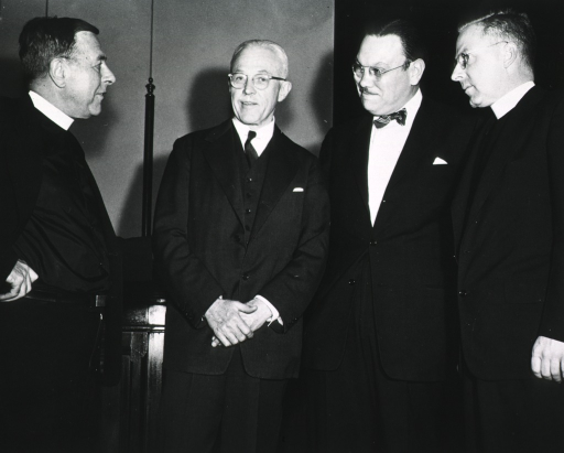 <p>Three quarter length, standing with officials of Georgetown University.</p>
