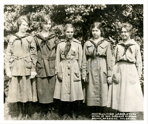 <p>Five girls scouts standing, each with their arms by their sides.</p>