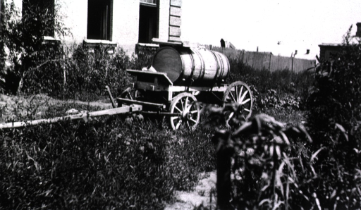 <p>A water wagon is located beside a building.</p>