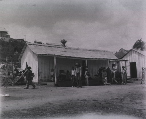 <p>Children and adults gather outside a Cuban house.</p>