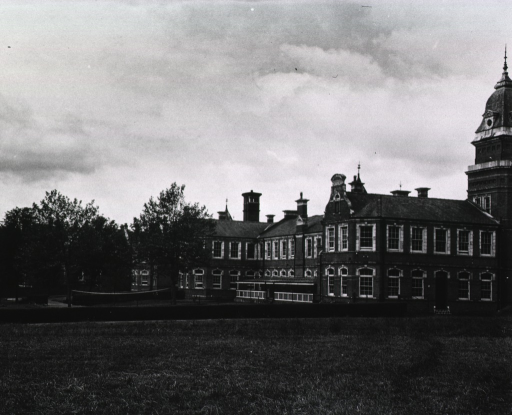 <p>Exterior view of the grounds and buildings of the 36th Station Hospital.  A badminton net is stretched between two trees.</p>