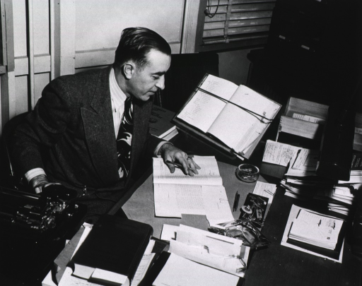 <p>Interior view:  Current List &amp; Index Division, Current List of Medical Literature.  Seated at his desk Dr. Filippi is reading an article.  Next to the desk is a typewriter; a calendar, ashtray and burning cigarette, the Psychiatry Dictionary, and stacks of journal articles are on the desk.</p>