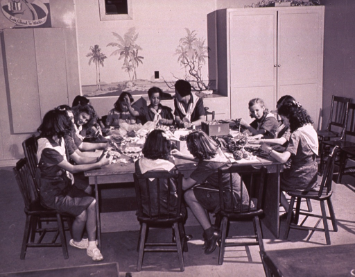 <p>A group of Girl Scouts in uniform seated around a square table making doll clothes (?).</p>