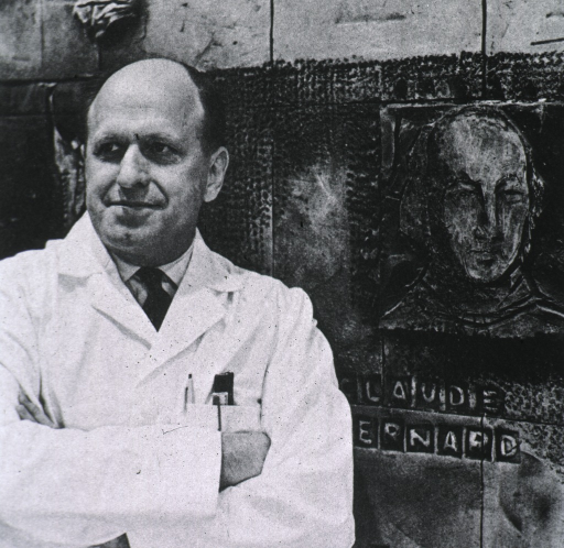 <p>Half-length, full face, arms crossed; wearing white lab coat; standing in front of a mural showing Claude Bernard.</p>