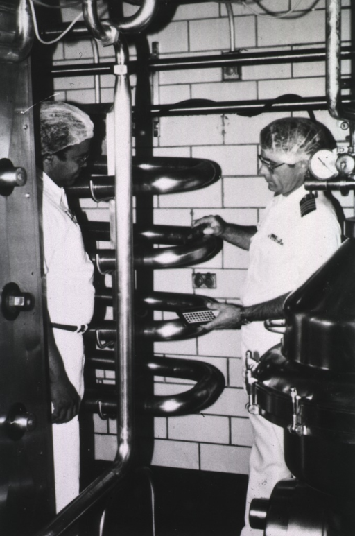 <p>A PHS officer wearing summer uniform and a plastic cap on his head inspects large, stainless steel tubing; another man stands on the left.</p>