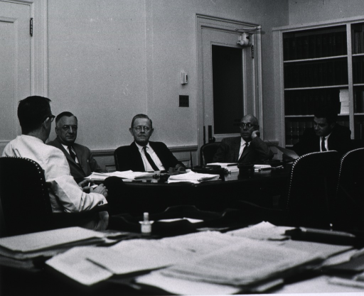 <p>Seated at a conference table are Dr. James A. Shannon (with back to camera), Dr. Justin Andrews, Dr. Stuart Sessoms, and others.</p>