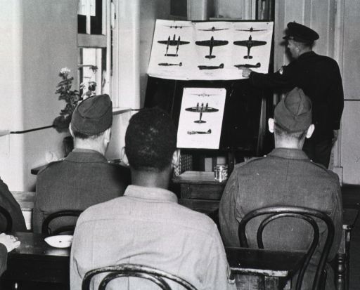<p>Several servicemen in uniform are shown from behind seated in a classroom.  At the head of the class, a serviceman stands and points at illustrations of airplanes posted on an easel.</p>