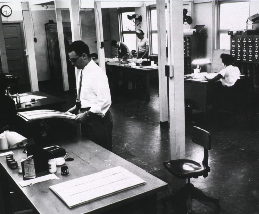 <p>Interior view: Current List of Medical Literature &amp; Index Division.  In the area are work tables with paste jars and a can of paper cement, a desk, and a card catalog against the wall,</p>