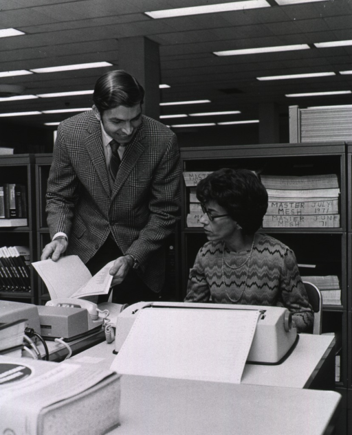 <p>Interior view: Bill Caldwell is standing next to the operator of the data entry computer.  The telephone receiver is sitting on the modem next to the keyboard.  July 1977 MeSH masters are on the shelf.</p>