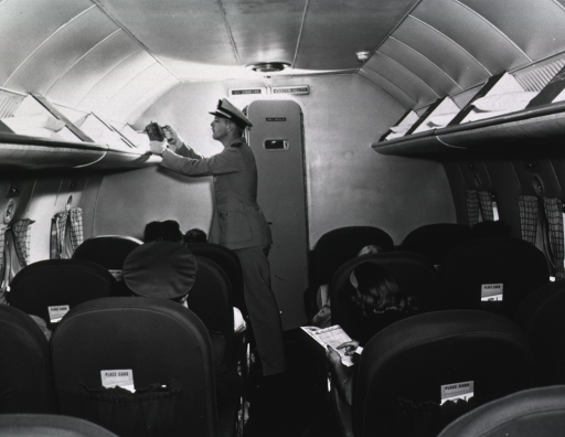 <p>A man wearing a uniform is spraying the overhead compartments on an airplane.</p>