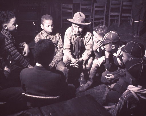 <p>A group of nine African American boys, some wearing Cub Scout uniforms, are sitting in a circle;  the boys appear to be listening to a Scout wearing a campaign hat (possibly the troop leader?).</p>