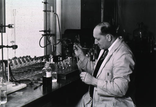 <p>Half-length, seated at laboratory bench.</p>