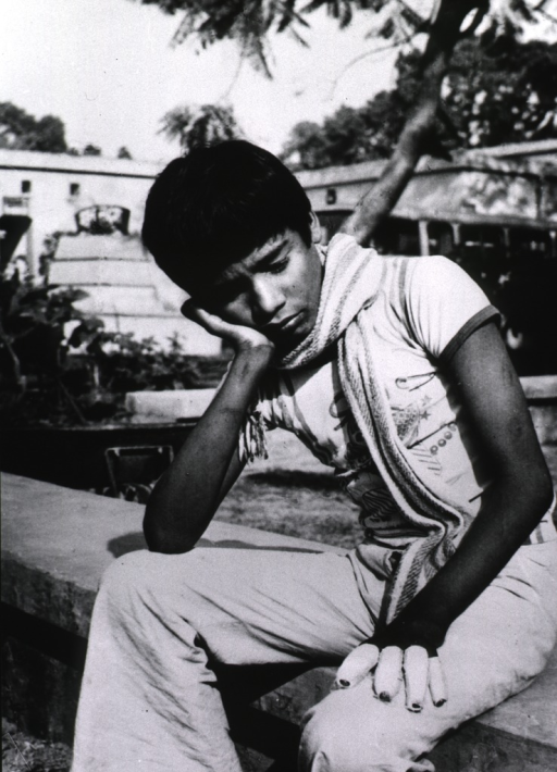 <p>A young man is sitting on a low wall; right elbow on his knee, and hand to cheek; the fingers of his left hand are bandaged.</p>
