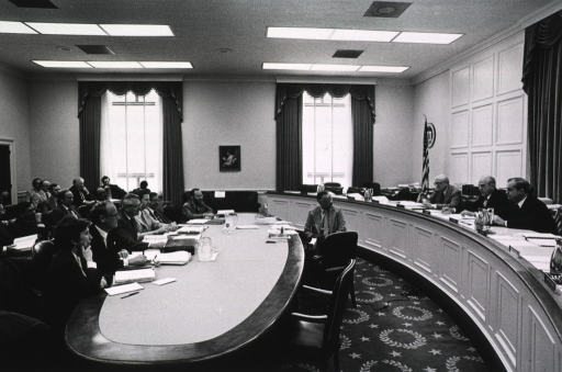 <p>Dr. Donald S. Fredrickson, director of the National Institutes of Health (NIH), is sitting at an oval table during the U.S. House labor and health appropriations subcommittee hearing. On the table are binders, notebooks, water pitchers, and a microphone.  Among those sitting with Dr. Fredrickson are Ellen Wormser, of the Dept. of Health, Education, and Welfare (DHEW), G. Donald Whedon, director of the National Institute of Diabetes and Digestive and Kidney Diseases (NIDDK), and Carl Levinthal.  George Payne is sitting by the window.  A stenographer is sitting between the oval table and the senator's bench.  Reps. William Natcher, from Kentucky's 2nd district, and Joseph Early, from Massachusetts' 3rd district, are seated at the bench with Henry Neil, the committee's clerk.  Under a picture between two large windows is a sofa.  There are three rows of people sitting behind the oval table.</p>
