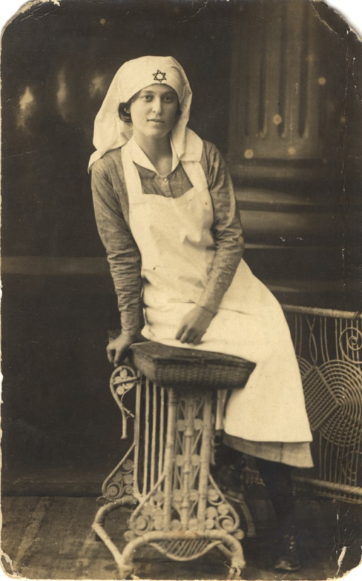 <p>Postcard featuring a black &amp; white photograph of a young female nurse in a uniform sitting on a stool. A hexagram (the Star of David) is on her head scarf.</p>