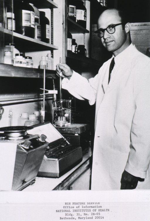 <p>Three quarter length, turned slightly to left; wearing glasses; wearing lab coat; standing beside lab apparatus, adjusting a buffer solution used in study of Selective Gamma-G Globulin Deficiency Syndrome; at Brigham Hospital, Boston.</p>
