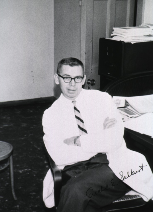 <p>Three quarter length, full face, seated in chair, arms folded, wearing white coat.</p>