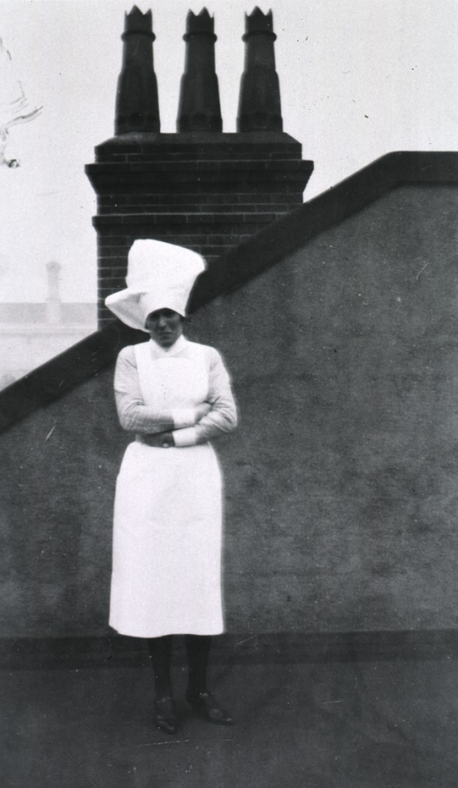 <p>Standing, full-length, on a roof(?), wearing a nursing uniform.</p>