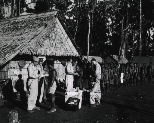 <p>A row of approximately two dozen indigenous men stand in a line next to a row of huts.  The men are in their bare feet and wear only shorts or wraps around their waists.  One of the servicemen sits at a table at the head of the line and takes notes, while the other four servicemen either stand or confer with the men.</p>