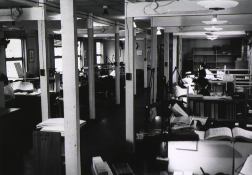 <p>Interior view: Current List of Medical Literature work area with people sitting at desks, stacked journals, book trucks, catalog card drawers.</p>