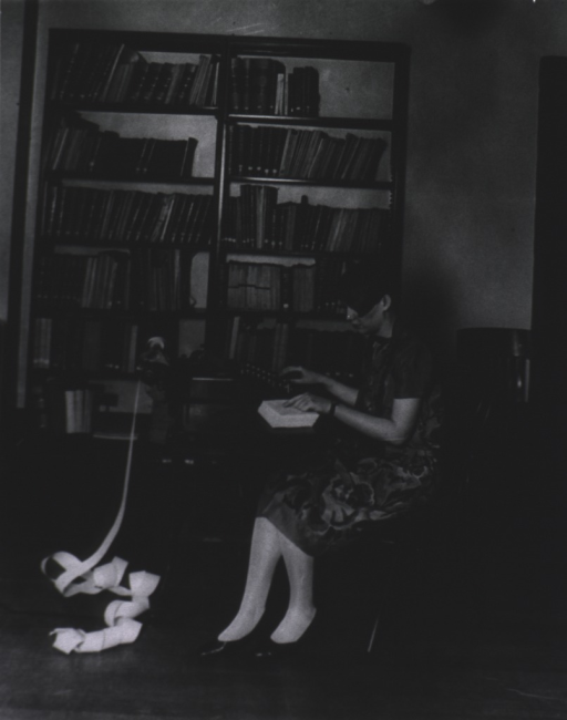 <p>Interior view of a room at the USPHS Statistical Office; a woman, seated at a small table, is using an adding machine; bookshelves in the background.</p>