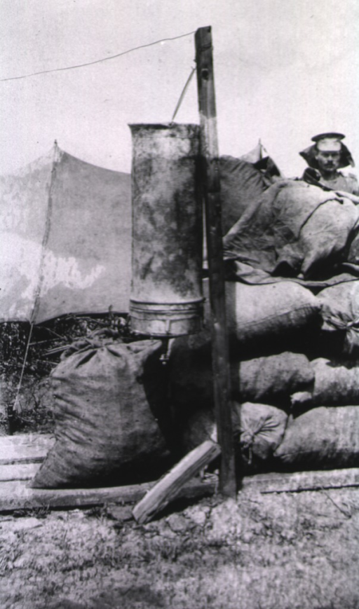 <p>A linen bag with an asbestos filter used for water is positioned beside sand bags.  A soldier stands behind the sand bags.</p>