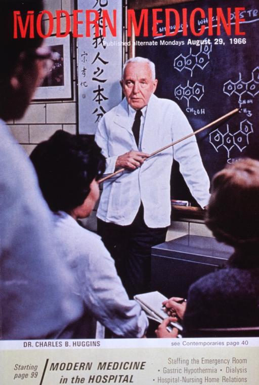 <p>Three fourths length, full face; in lab coat; standing pointing to chemical symbols on blackboard as he lectures to a class.</p>