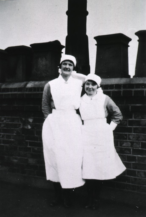 <p>Standing, full-length, on a roof, wearing nursing uniforms.</p>