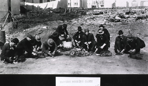 <p>View of 12 ratcatchers squatting on the ground attaching tags to dead rats to identify where, when, and by whom  they were collected; a man in the center dips a rat trap into a bucket of antiseptic solution.</p>
