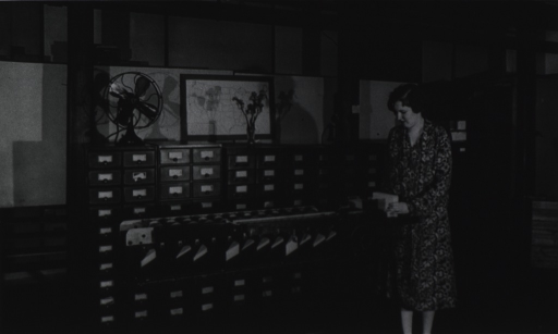 <p>Interior view of a room at the USPHS Statistical Office; a woman is operating a card sorter that is placed in front of several cabinets of card drawers.</p>