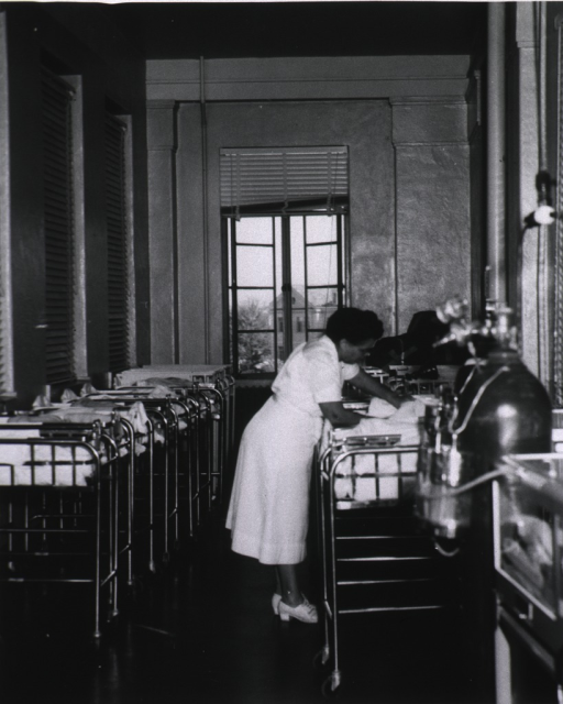 <p>An African American nurse is at the bedside of a newborn.  A large oxygen tank is in the foreground.</p>