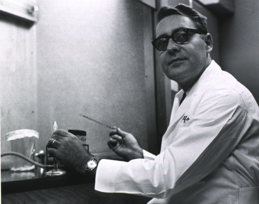 <p>Half length; turned to left, face forward; wearing glasses; in lab coat, heating test tube over bunsen burner, pipette in right hand.</p>