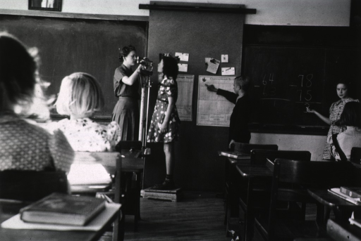 <p>Primary school classroom scene at the Black Hills Teachers College, showing a female student being weighed by the student teacher and a male student pointing to a growth chart.</p>