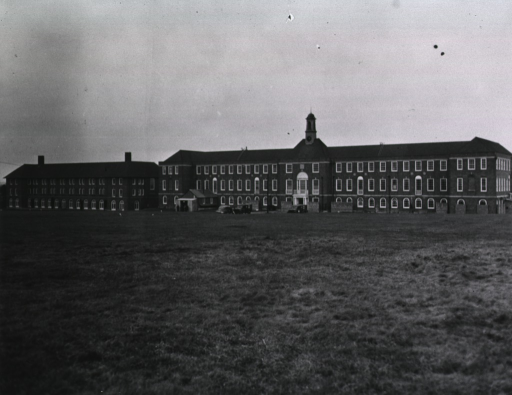 <p>Frontal view of the three-story 38th Station Hospital.  Several army ambulances can be seen parked in front of the brick building.  A few men stand next to a small wooden structure in front of the building.</p>