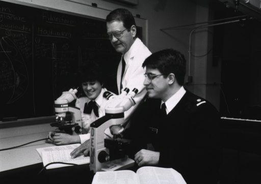 <p>Interior view of parasitology laboratory/classroom: a man wearing a white lab coat instructs two students wearing uniforms; they sit at tables with microscopes in front of them; hookworm illustrations are visible on a blackboard in the background.</p>