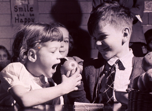 <p>Children in a school cafeteria; a girl is about to take a bite out of a boy's apple.</p>