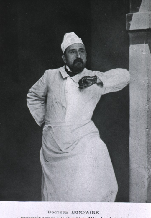<p>Three-quarter length, full face, standing, arm against post, wearing white jacket, apron and cap.</p>