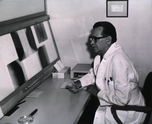 <p>Three-quarters length, turned to left, wearing lab coat and glasses, seated in front of shadow box with x-rays displayed.</p>