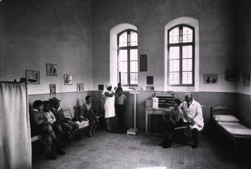 <p>Interior view of an infirmary showing a nurse measuring a student and the doctor examining another student while several others await their turns.</p>